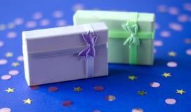 Två askar med gåvor på en blå bakgrund royaltyfri foto