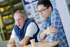 Två attraktiva byggnadsarbetare som har kaffeavbrottet royaltyfria bilder