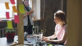 Två attraktiva flickor arbetar tillsammans i modernt vindkontor Den blonda kvinnan skriver på bärbar datorsammanträde på tabellen arkivfilmer