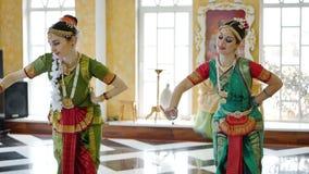 Två attraktiva flickor i en sari dansar en nationell dans arkivfilmer