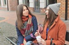 Två attraktiva flickor sitter på en bänk i gatan arkivfoton