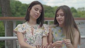 Två attraktiva flickor som sitter utomhus tillsammans att prata om ny manikyr och att visa fingrar och, spikar flickv?nner stock video