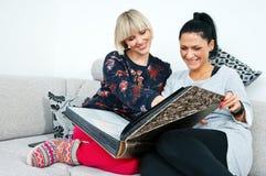 Två attraktiva kvinnavänner med fotoalbumet Royaltyfri Fotografi