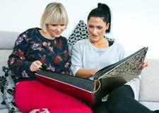 Två attraktiva kvinnavänner med fotoalbumet Royaltyfria Bilder