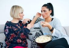Två attraktiva kvinnavänner med popcornsamtal Arkivbilder