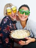 Två attraktiva kvinnavänner med roliga exponeringsglas och popcorn Royaltyfri Bild