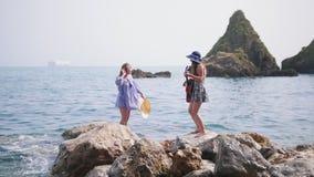 Två attraktiva kvinnor blir på stenen i hav ett av dem som dansar lager videofilmer