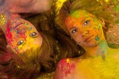 Två attraktiva kvinnor i färgerna av Holi Royaltyfria Bilder