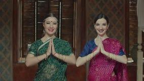 Två attraktiva kvinnor i sari med stråla leenden