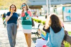 Två attraktiva kvinnor i staden som tillsammans pratar arkivbild