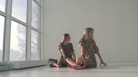 Två attraktiva kvinnor som bär yogakläder som öva yoga, poserar lager videofilmer