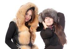 Två attraktiva kvinnor som kläs för vinter Royaltyfri Fotografi