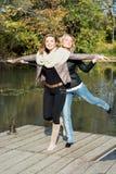 Två attraktiva kvinnor som poserar vid dammet i hösten, parkerar royaltyfria bilder