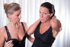 Två attraktiva kvinnor som sätter på deras halsband royaltyfria bilder