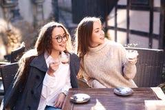Två attraktiva kvinnor som sitter i gatakafét royaltyfria bilder