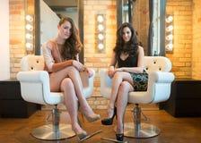 Två attraktiva modeller i salongstolar Arkivbilder