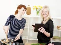 Kvinnliga vänner som lagar mat i kök royaltyfri fotografi
