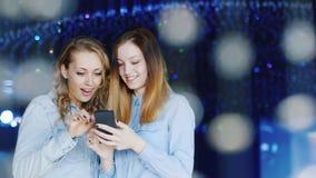 Två attraktiva unga kvinnor tycker om en smartphone i en nattklubb De står omkring av glass prydnader stock video