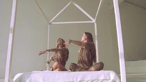 Två attraktiva yogakvinnor som sitter i olik yoga, poserar stock video