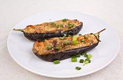 Två aubergine som är välfyllda med ost och champinjoner Arkivfoton