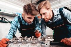 Två auto mekaniker kontrollerar detaljen i garage arkivbild