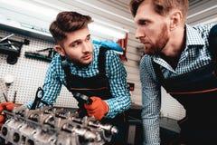 Två auto mekaniker kontrollerar detaljen i garage arkivbilder