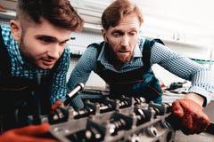 Två auto mekaniker kontrollerar detaljen i garage arkivfoton