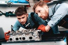 Två auto mekaniker kontrollerar detaljen i garage fotografering för bildbyråer