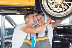 Två auto mekaniker som analyserar kanterna av en lyftbil fotografering för bildbyråer