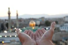 Två av öppna händer som ska bes framme av gravvalvet av Zeinab Arkivbilder