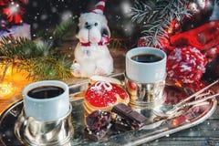 Två av tumvantena och marmeladen för pajdeg med svart kaffe på en hemtrevlig jultabell Närbild snow Royaltyfri Foto