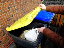 Två avfallbehållare i trädgården av det privata huset för plast- och pappers- avfall med en man som kastar en avfallpåse i en gul fotografering för bildbyråer