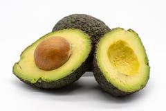 Två avokadon, en hel frukt och som halveras med stenen arkivfoto