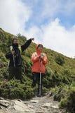 Två bärande ytterkläder för barnpar står på kullen, och de manliga vandringpunkterna på någonstans som låter den kvinnliga fotvan royaltyfri bild