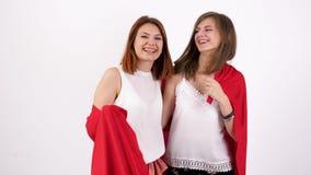 Två bästa kvinnliga vänner som täcker dem själv med en röd filt arkivfilmer
