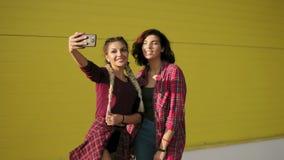 Två bästa vänflickor som har gyckel och gör selfieanseende vid den gula väggen Två hipsterflickor som tar selfiefoto lager videofilmer