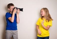 Två bästa väntonår som hemma gör fotoet på deras kamera och att ha gyckel tillsammans, glädje och lycka royaltyfria foton
