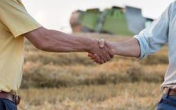 Två bönder som skakar händer i fält royaltyfria bilder