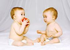 Två babys kopplar samman på sängen Arkivbild