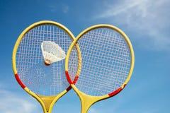 Två badmintonracket och fjäderbollflyg arkivbilder