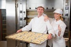 Två bagare med lagget som är full av kringlor Arkivbilder
