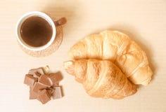 Två bakade giffel med en kopp kaffe och en choklad Fotografering för Bildbyråer