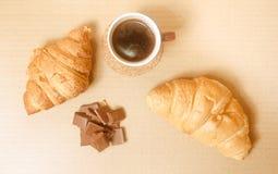 Två bakade giffel med en kopp kaffe och en choklad Royaltyfri Bild