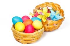 Två bakade korgen med påsken färgade ägg och pappers- blommor Arkivfoto