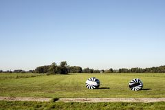 Två baler av hö som slås in i svartvit randig plast- royaltyfri bild