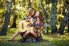 Två barn danar flickor med gitarren i sommarskog Arkivbild