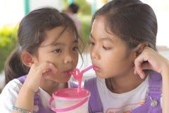 Två barn dricker fruktfruktsaft Royaltyfri Bild