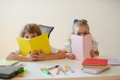 Två barn klasskompis, pojke och flicka, sitter på det samma skrivbordet arkivbild