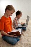 Två barn med böcker och bärbar dator Royaltyfri Foto