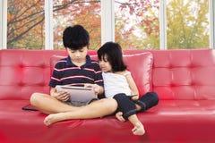 Två barn med den digitala minnestavlan på soffan Arkivbild